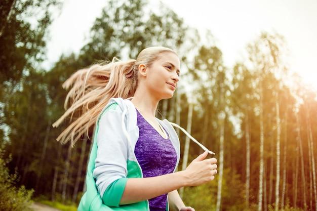 Corridore ragazza felice e in buona salute sulla strada, jogging mattutino