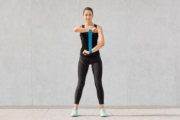 Corridore sportivo giovane donna con elastico, fa esercizi per le mani, vestito con macchie, scarpe da ginnastica, ha i capelli scuri, vuole avere un corpo muscoloso, modelle sul muro di cemento grigio al coperto
