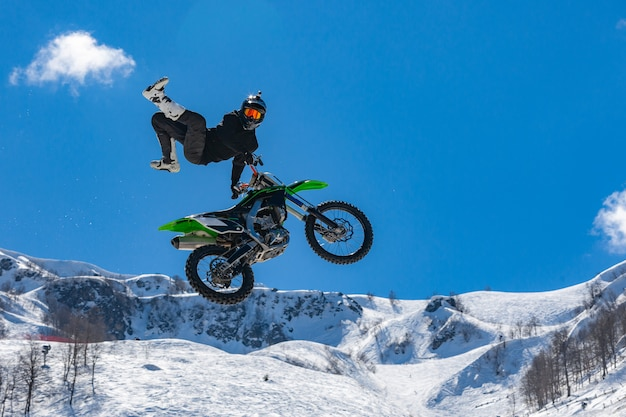 Corridore su una moto in volo in montagne innevate