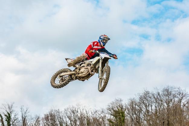 Corridore su una moto in volo, salta e decolla su un trampolino contro il cielo.