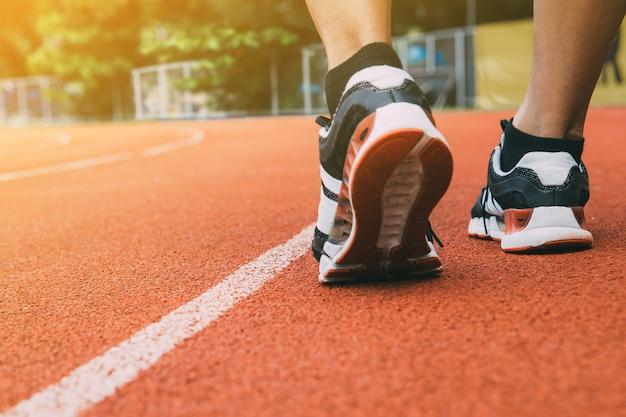 Corridore su una pista con un primo piano delle scarpe.