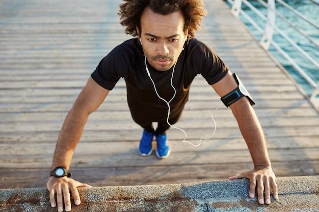 Corridore uomo dalla carnagione scura in abiti sportivi neri in piedi nella posizione della plancia che si riscalda prima dell'allenamento cardio sul molo al mattino.