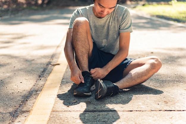 Corridore uomo legare lacci delle scarpe nel parco