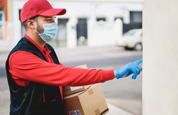 Corriere con maschera protettiva e guanti che consegna pacchi a casa durante il periodo di pandemia di coronavirus - concetto di prevenzione della diffusione di covid 19