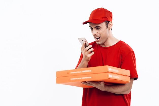 Corriere con pizza in grida uniforme in telefono.