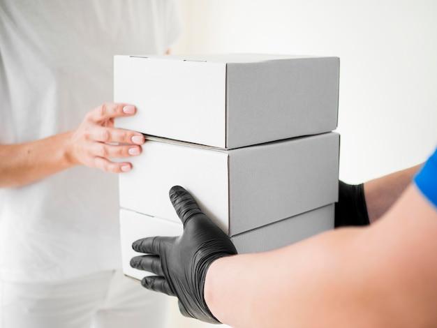 Corriere del primo piano con i guanti che consegnano le scatole