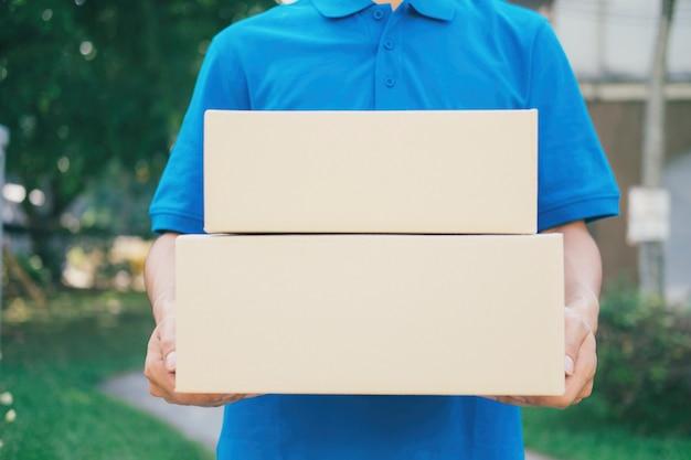 Corriere del servizio di consegna in piedi davanti alla casa con le scatole.