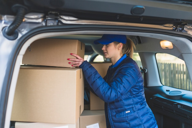 Corriere femminile con scatole in auto