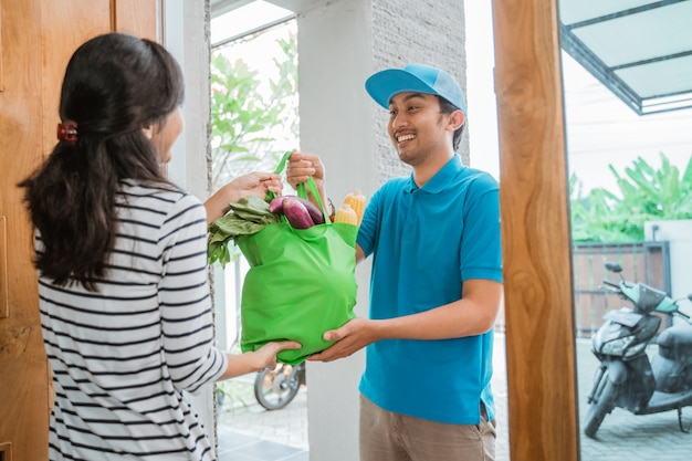 Corriere maschio consegna di generi alimentari al cliente