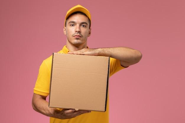 Corriere maschio di vista frontale in scatola di consegna del cibo della tenuta uniforme gialla sullo scrittorio rosa