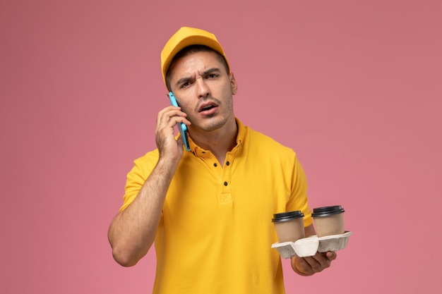 Corriere maschio di vista frontale in tazze di caffè di consegna della tenuta della tenuta uniforme gialla che comunicano sul telefono sui precedenti rosa