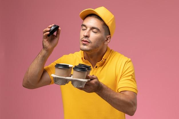 Corriere maschio di vista frontale in tazze di caffè di consegna della tenuta uniforme gialla che li odorano sullo scrittorio rosa