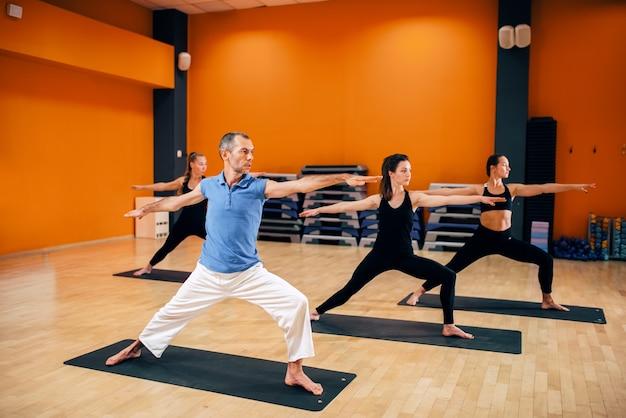 Corso di formazione yoga, gruppo femminile con allenatore maschio in azione in palestra. yogi esercizio al coperto
