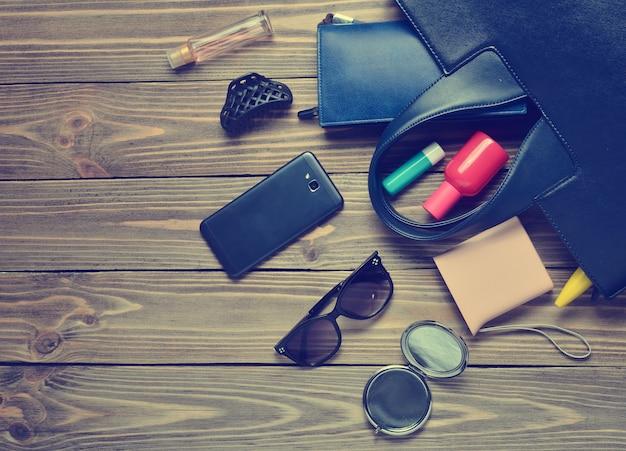 Cosa c'è nella borsa da donna? accessori alla moda femminile su un legno.