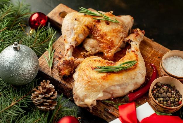 Cosce di pollo alla griglia di natale con spezie ed erbe aromatiche, con alberi di natale e giocattoli, facchini su uno sfondo di pietra.