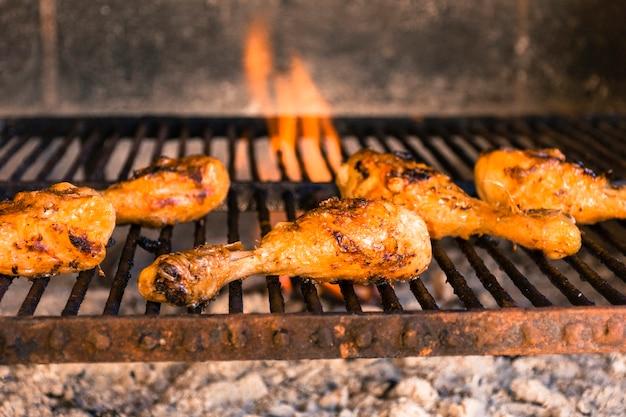 Cosce di pollo alla griglia sulla griglia calda con fuoco pesante
