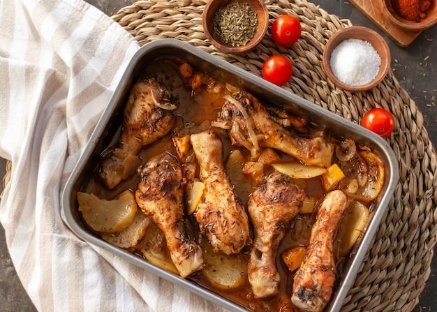 Cosce di pollo arrostite sulla teglia in metallo con patate, cipolla. pomodori con spezie.