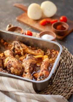 Cosce di pollo arrostite sulla teglia in metallo con patate, cipolla. pomodori e alcune spezie.