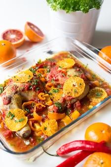 Cosce di pollo con pomodori, peperoni e arance