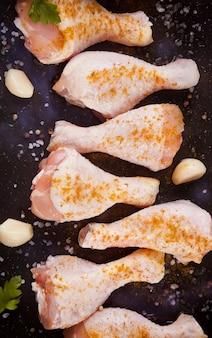 Cosce di pollo crude crude con spezie ed erbe aromatiche
