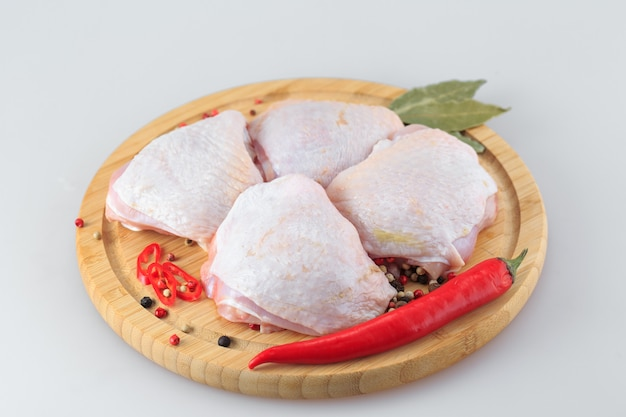 Cosce di pollo crude su bianco