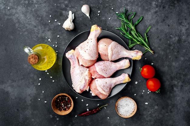 Cosce di pollo crudo con spezie su uno sfondo di pietra