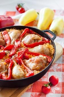 Cosce di pollo e cosce al forno su un letto di riso e peperone rosso