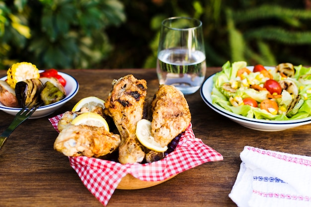 Cosce di pollo e insalata servite all'aperto