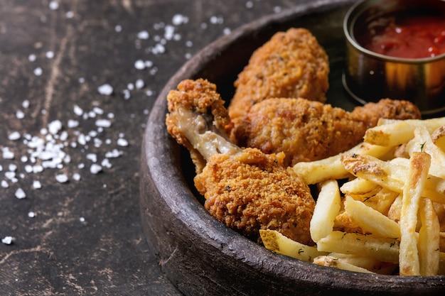 Cosce di pollo fritto con patatine fritte