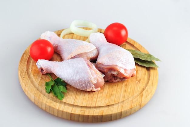 Cosce di pollo grezze su uno sfondo bianco