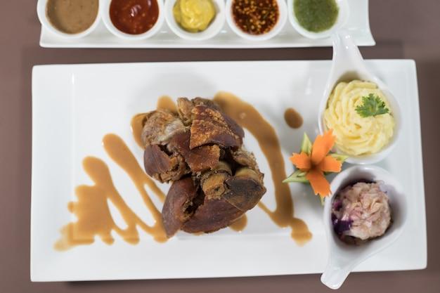Coscia di maiale fritto profonda cucinata in stile tailandese con pesce e salse mayo