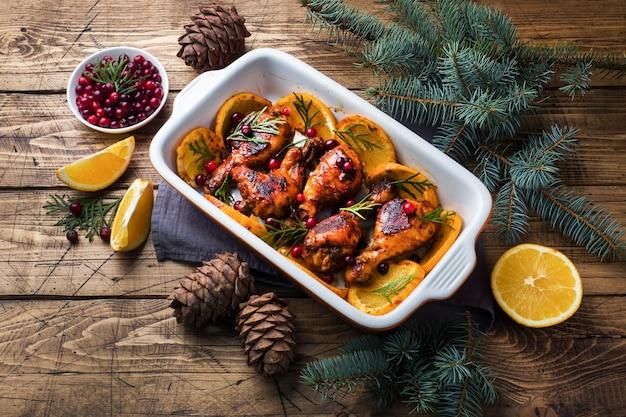 Coscia di pollo al forno con arance e mirtilli rossi in una teglia tabella dell'alimento di natale con le decorazioni.