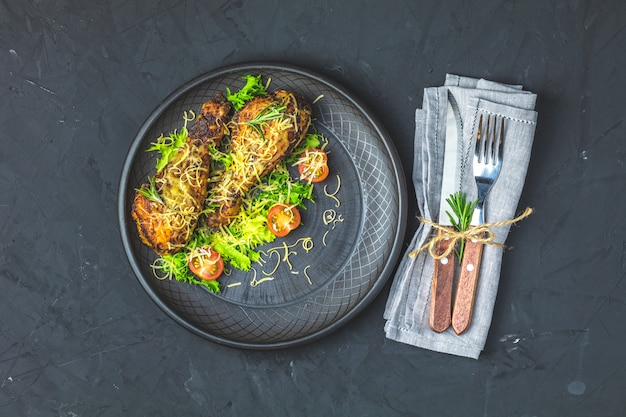 Coscia di pollo al forno in un piatto di ceramica nera
