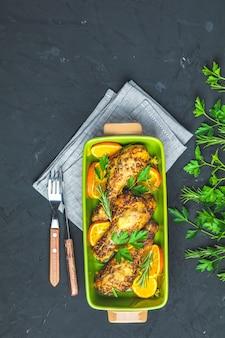 Coscia di pollo al forno in un piatto verde con arancia e rosmarino
