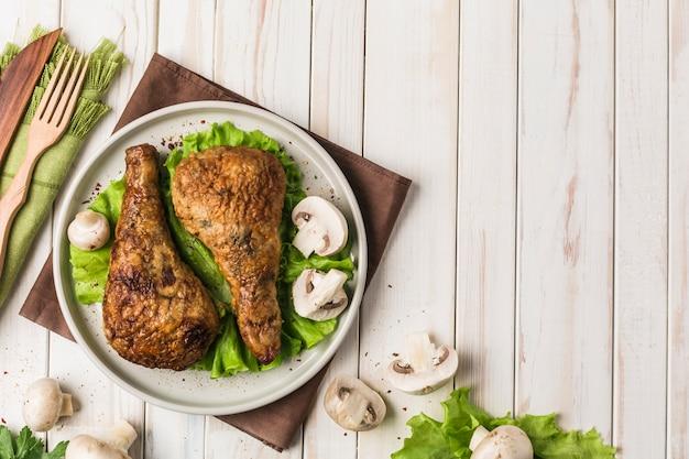 Coscia di pollo fritto farcita con piatto piano di funghi con foglia di lattuga su legno chiaro.