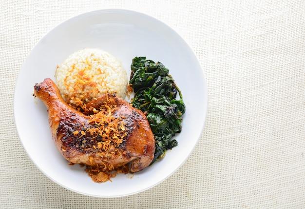 Coscia di pollo marinata con salsa piccante al peperoncino ed erbe aromatiche, servita con riso cotto e spinaci.