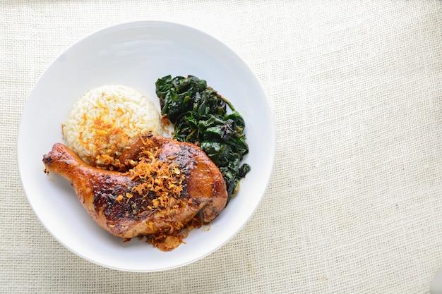 Coscia di pollo marinata con salsa piccante al peperoncino ed erbe aromatiche, servita con riso cotto e spinash.