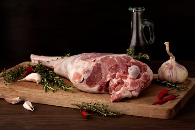 Cosciotto d'agnello pronto per arrostire con aglio ed erbe aromatiche