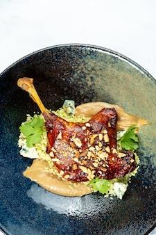 Cosciotto d'anatra confit con burro di arachidi e formaggio blu dor in elegante ciotola scura sul tavolo di marmo. pranzo gourmet. cucina francese.