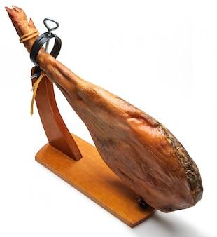 Cosciotto intero di prosciutto iberico spagnolo in supporto di legno (jamoneror). isolato