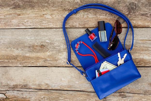 Cose dalla borsa aperta della signora. cosmetici, soldi e accessori da donna caddero dalla borsetta blu. vista dall'alto.