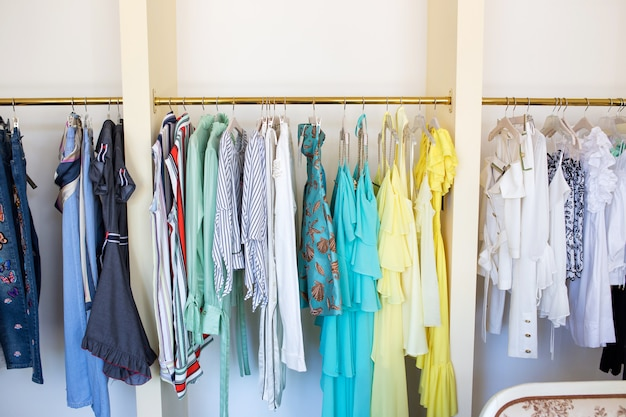 Cose femminili di colore su una gruccia. nuova collezione estiva nel negozio.