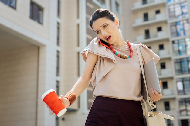 Così occupato. bella donna compra parlando al telefono mentre si tiene un bicchiere di caffè