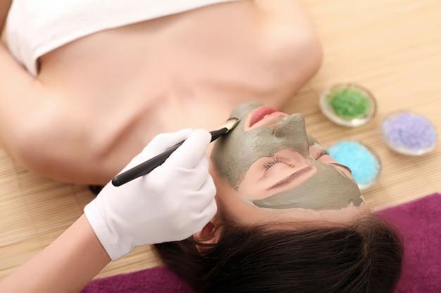 Cosmetica spa per il viso. bella bruna in un salone spa