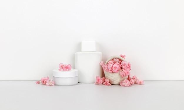 Cosmetici con fiori rosa, bottiglia contengono