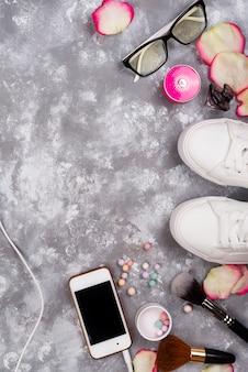 Cosmetici con profumo, telefono e scarpe da ginnastica su uno sfondo grigio con spazio di copia