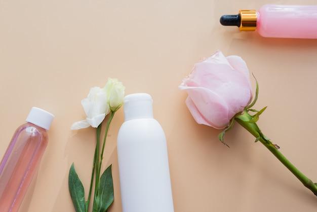 Cosmetici da ingredienti naturali ed estratti di fiori e rose su uno sfondo beige.