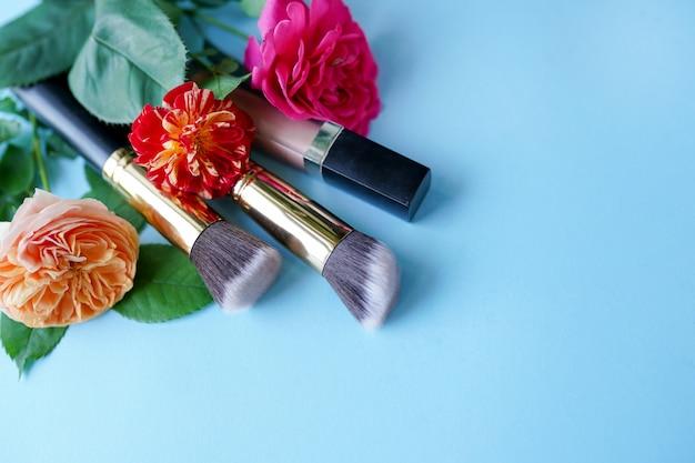 Cosmetici decorativi con i fiori rossi e rosa sul blu