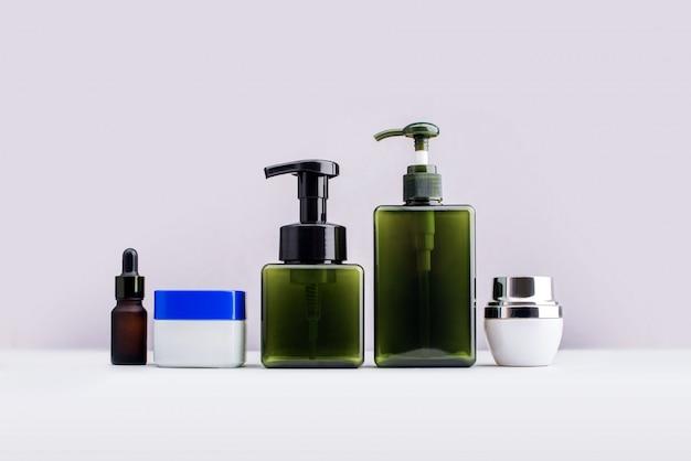Cosmetici delle bottiglie e prodotti di bellezza isolati su bianco