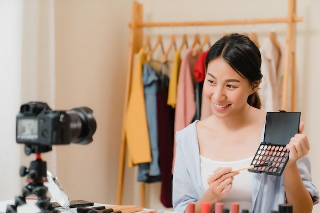 Cosmetici di bellezza presenti di bellezza di blogger che si siedono nella macchina fotografica anteriore per registrare video.
